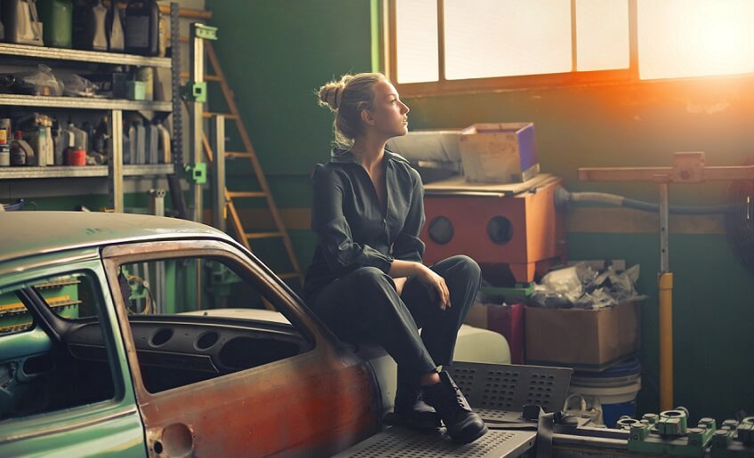 girl sitting in messy garage